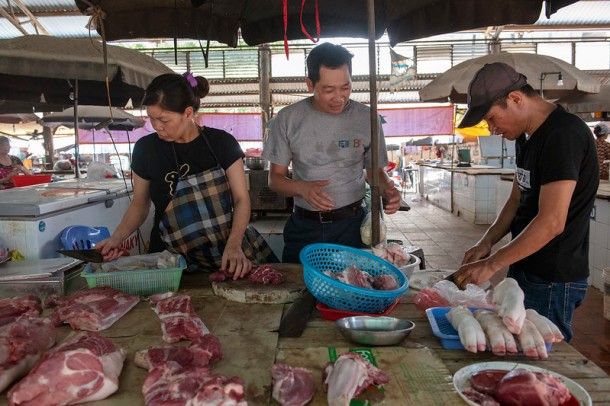 Hung Nguyen, scientist ILRI food system specialist visiting Dong Xa Market.
